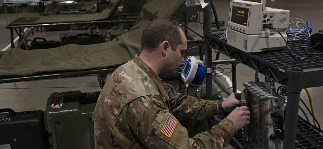 Medical brigade specialist sets up medical devices in an army-mobilized field hospital.